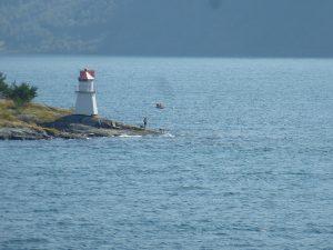 Leuchtturm mit Ruderboot im Hintergrund