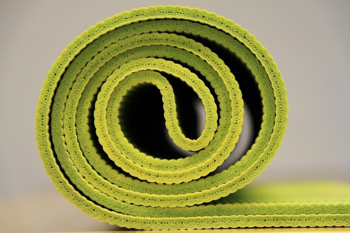 aufgerollte grüne Yoga-Matte vor weißem Hintergrund